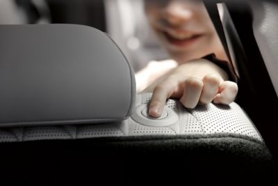 Interior view of the new Hyundai Santa Fe 7 seat SUV showing a child adjusting the headrest
