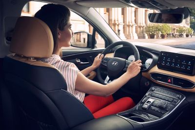 Interior view of the new Hyundai Santa Fe 7 seat SUV showing a woman driving down the highway.